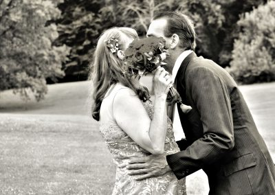 Bride and Groom Steal a Kiss Behind Flowers